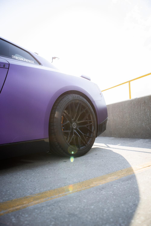 purple car on gray asphalt road