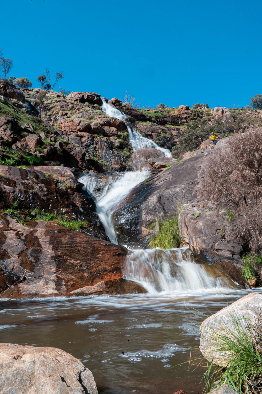 water falls on brown rocky mountain under blue sky during daytime