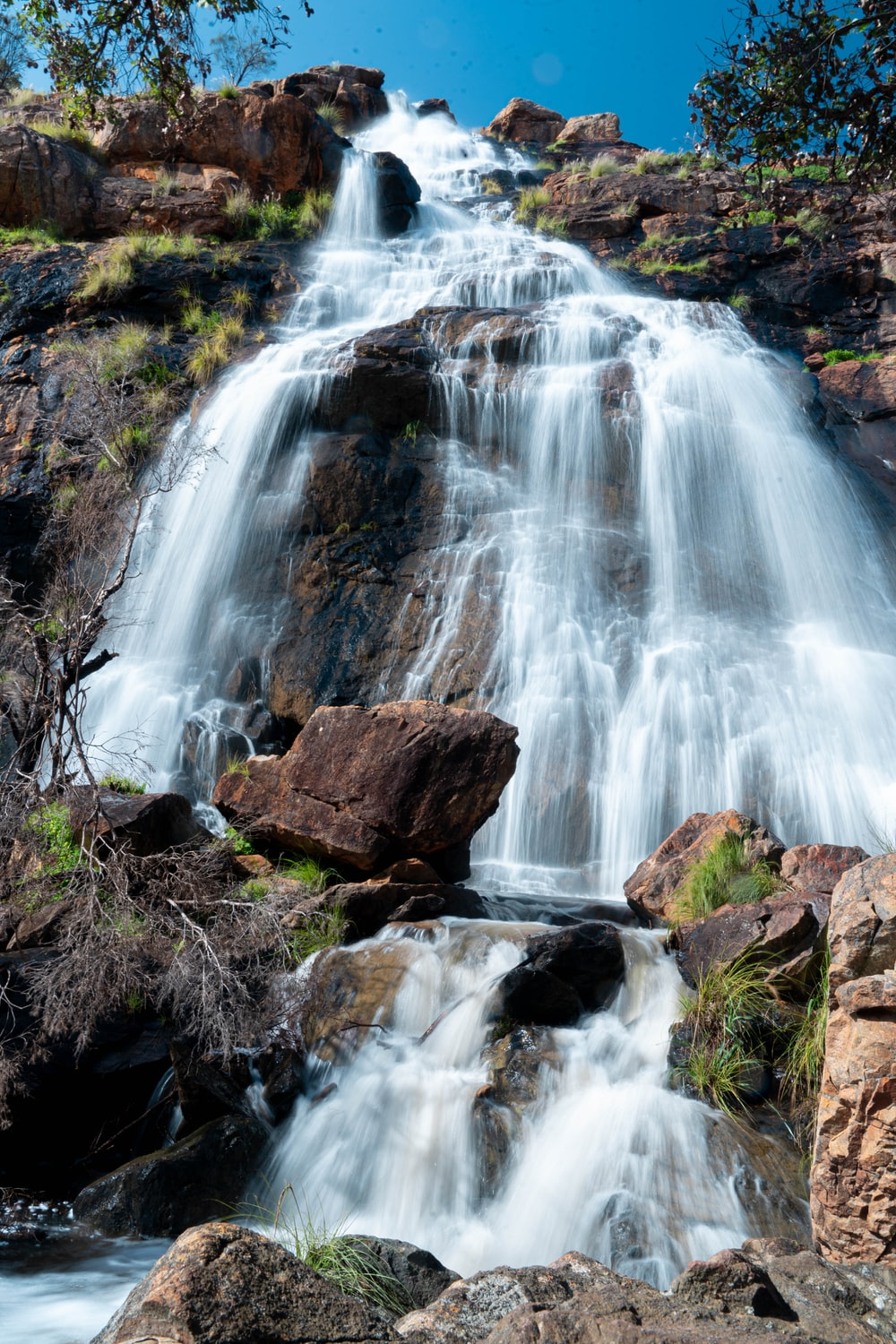 water falls on brown rocky mountain during daytime