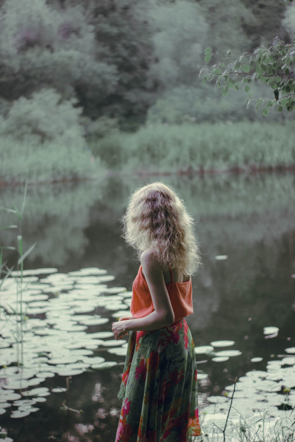 girl in red and green dress standing on water during daytime