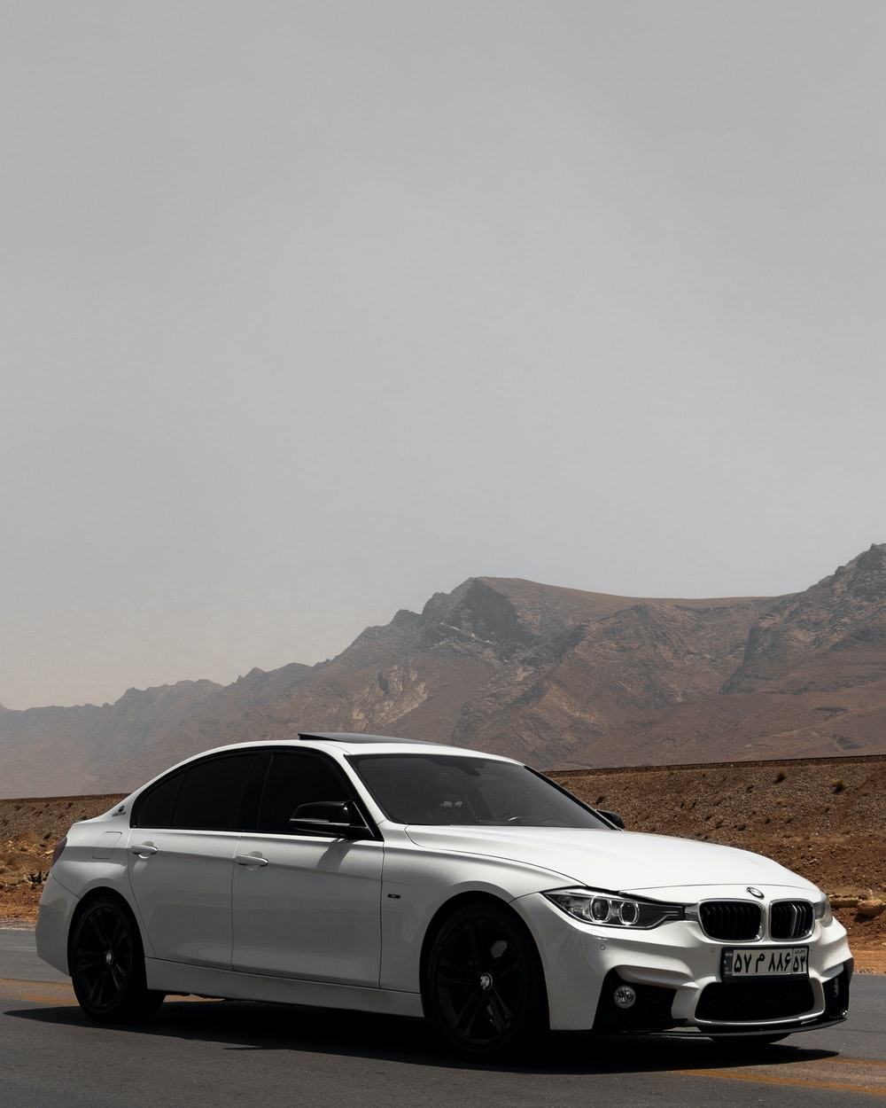 white bmw x series on brown field during daytime