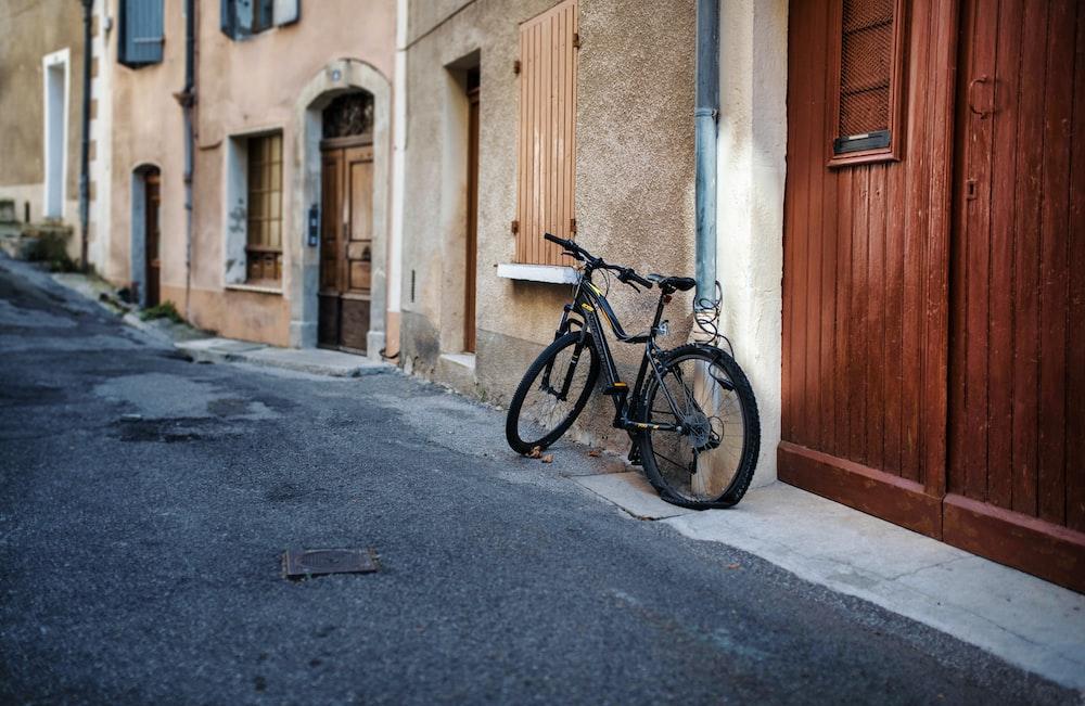 black city bike parked beside brown wooden door
