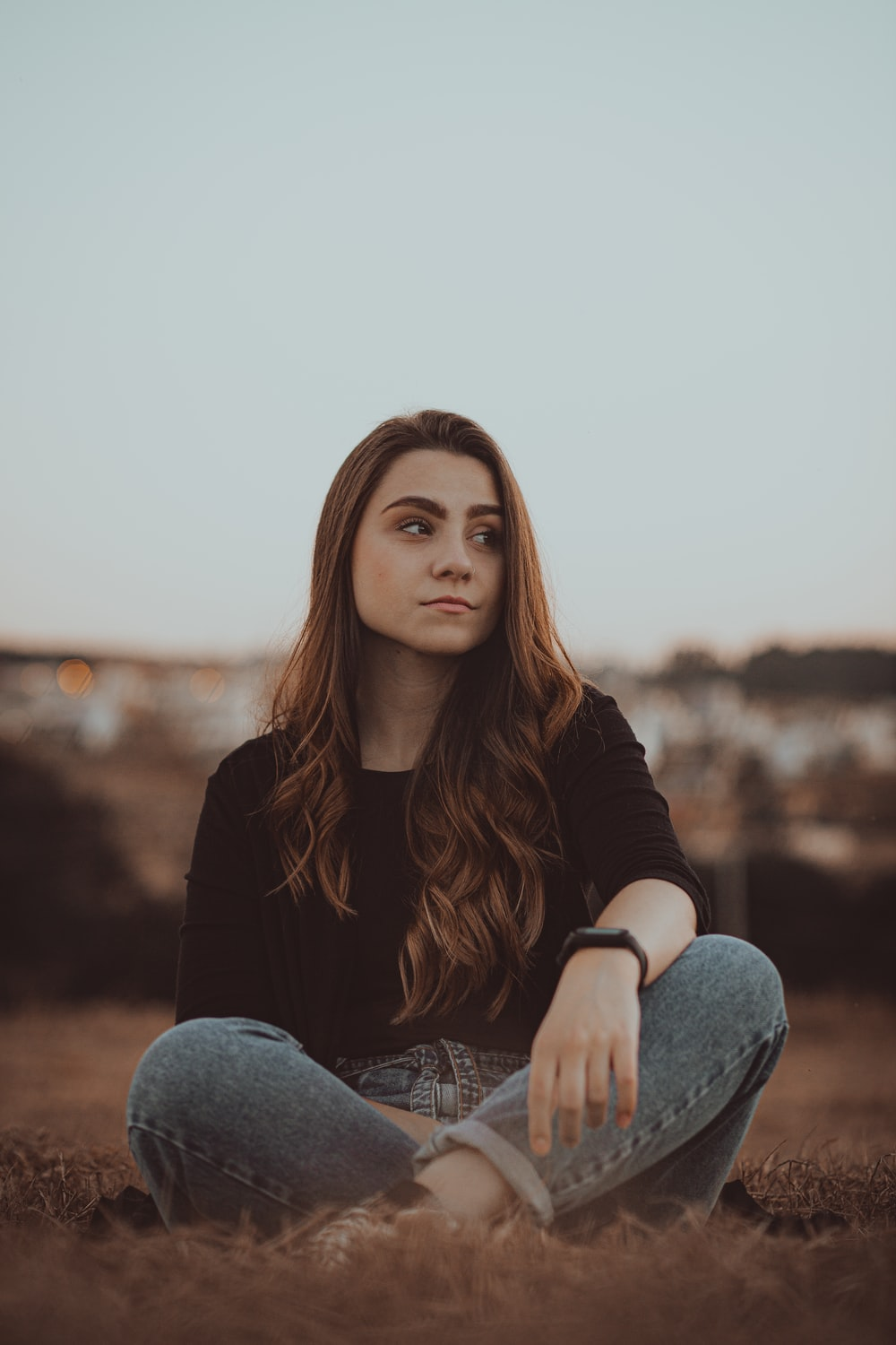 woman in black long sleeve shirt and blue denim jeans sitting on brown rock during daytime