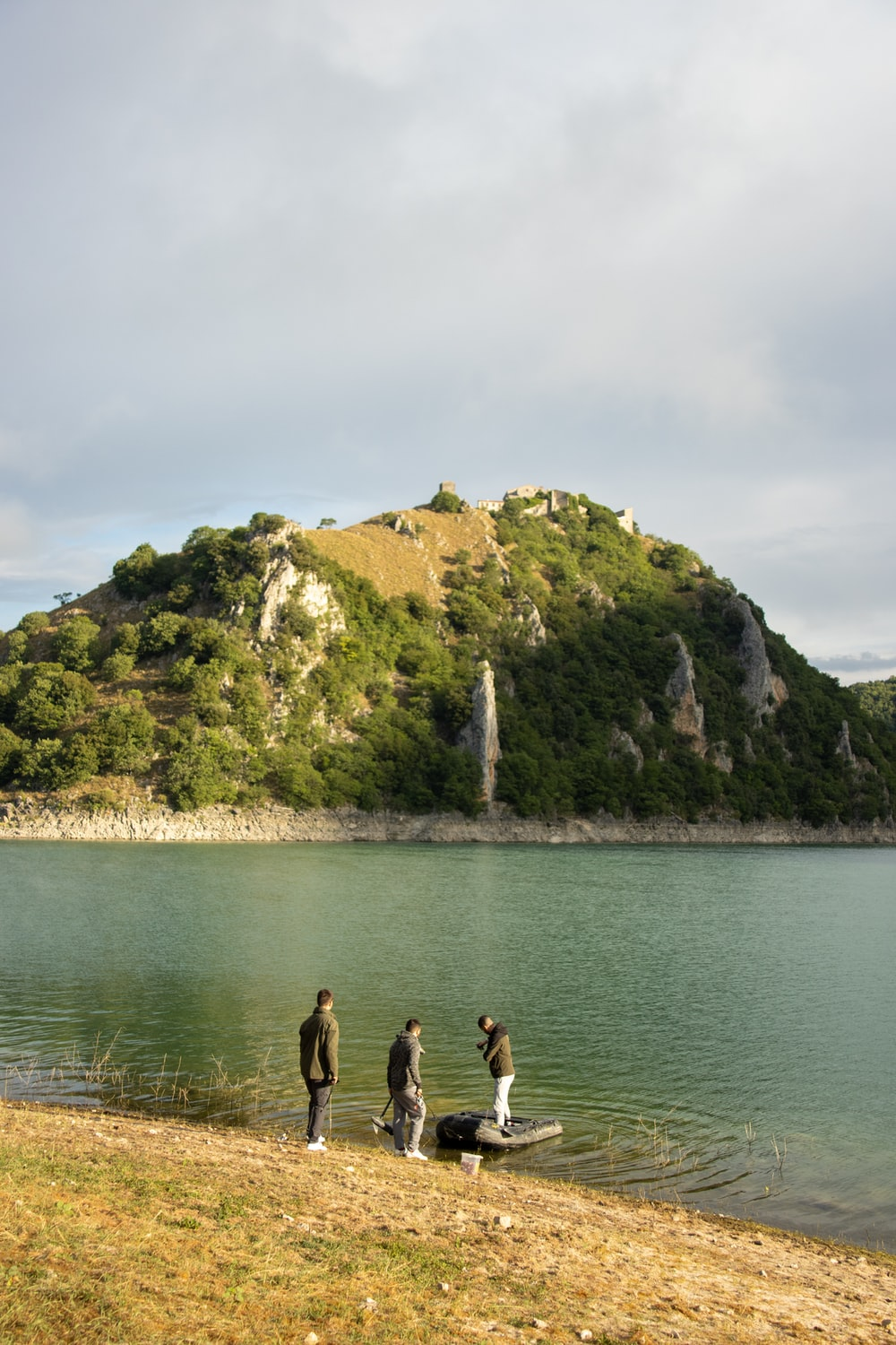 2 men standing on rock formation near body of water during daytime