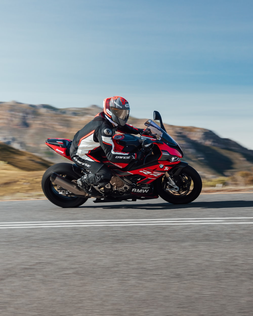 man in black and red motorcycle suit riding on black sports bike on gray asphalt road
