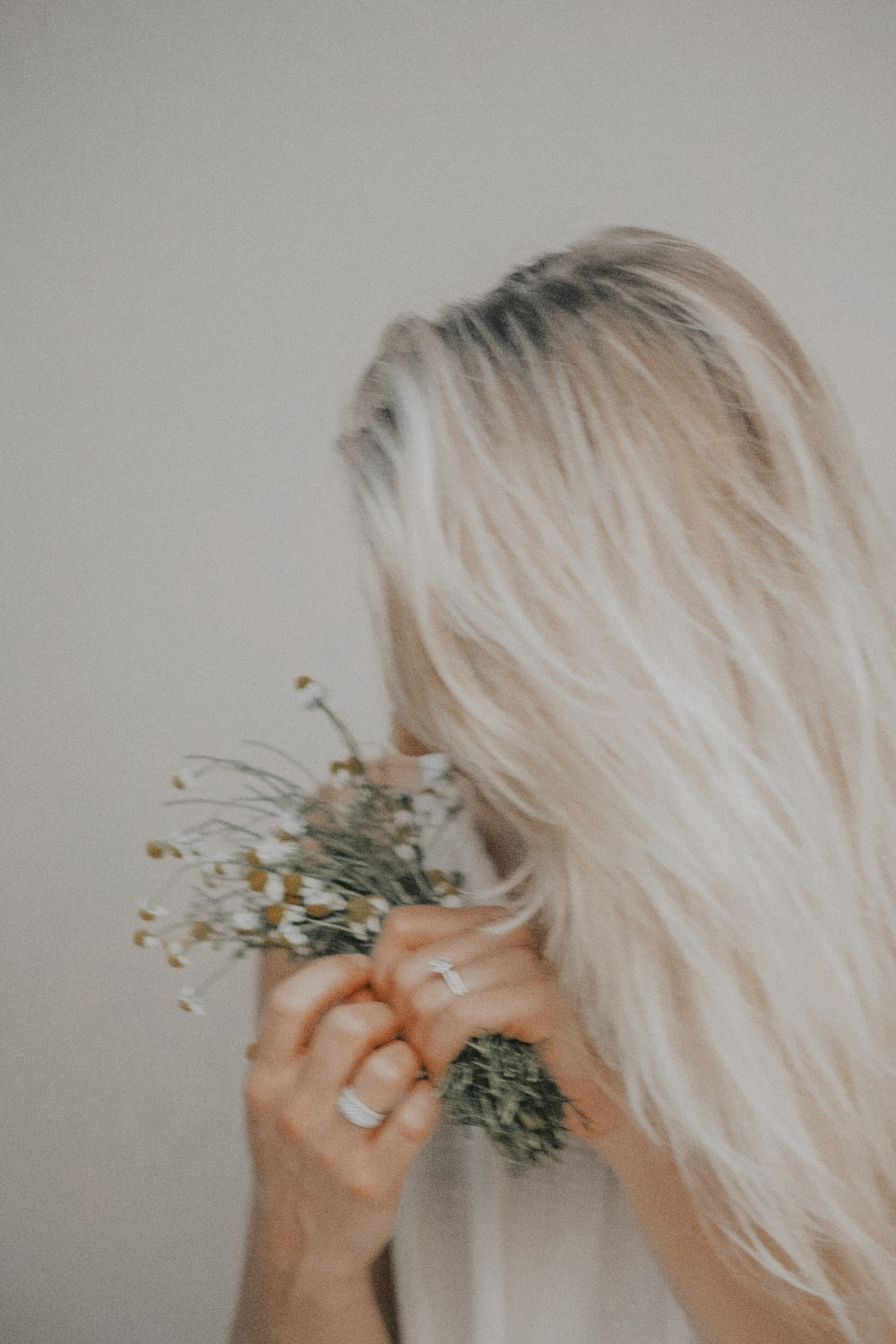 woman holding white flowers in white painted room
