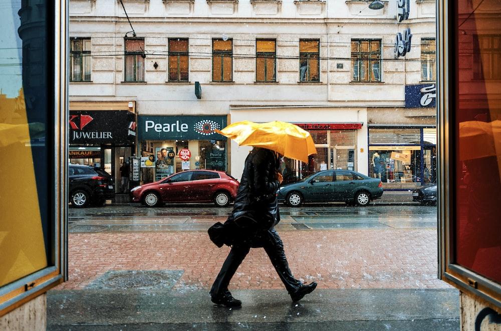 person in black jacket and black pants holding yellow umbrella walking on sidewalk during daytime