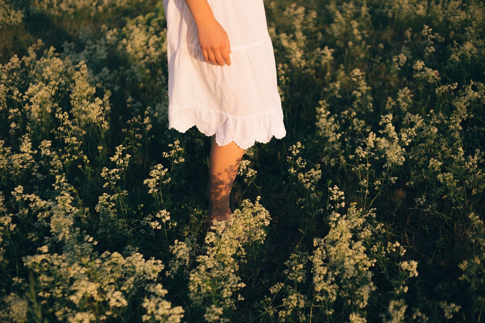 woman in white mini dress standing on green grass field during daytime