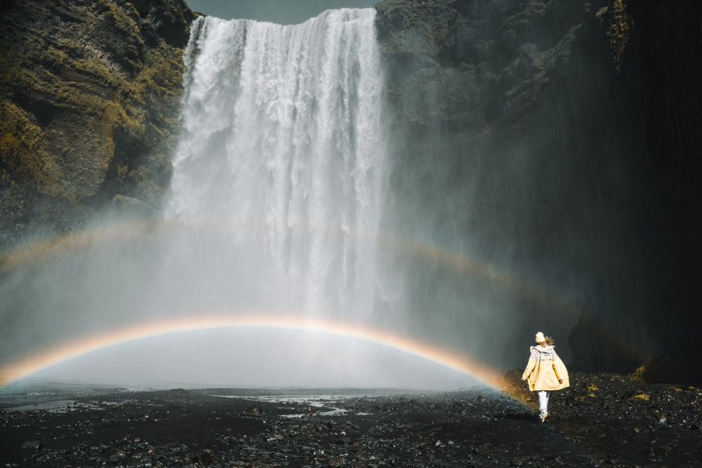 person in yellow jacket standing in front of waterfalls during daytime