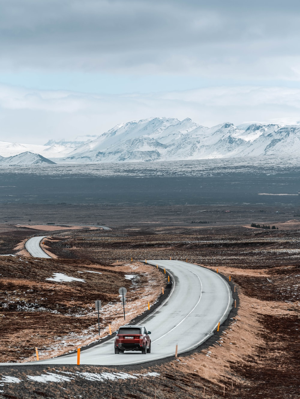 white car on road near snow covered mountain during daytime