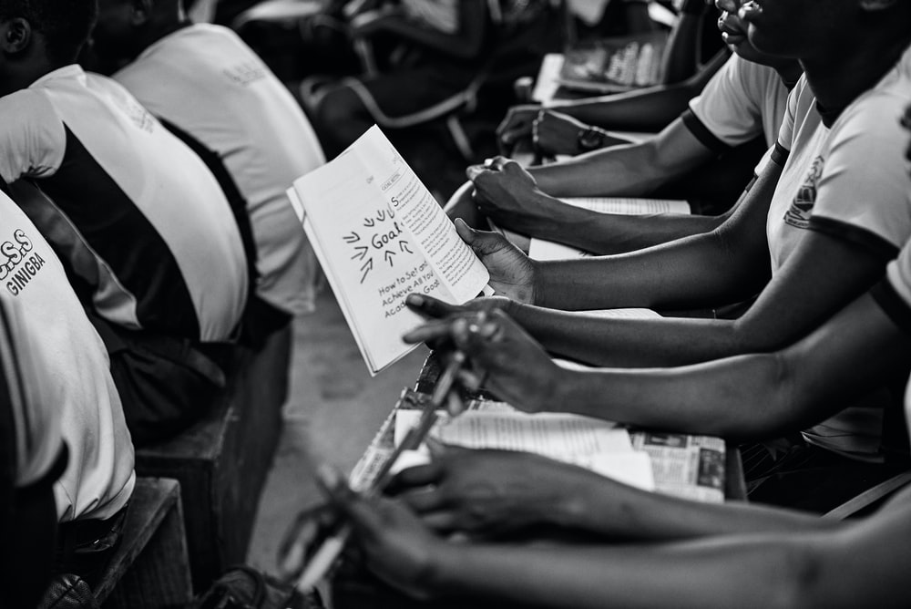 grayscale photo of people holding papers