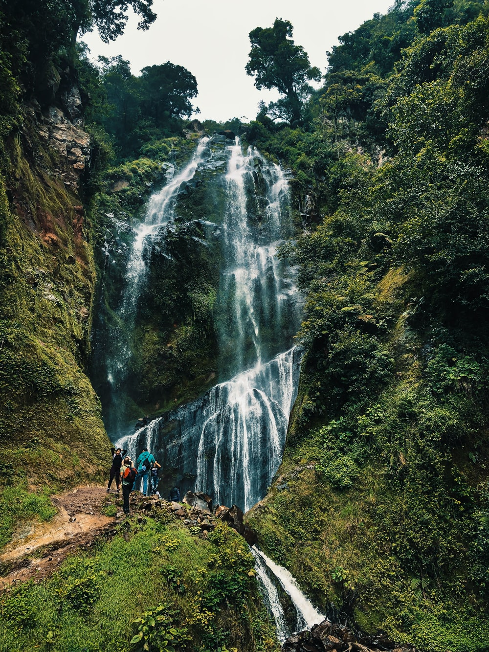 people walking on pathway near waterfalls during daytime