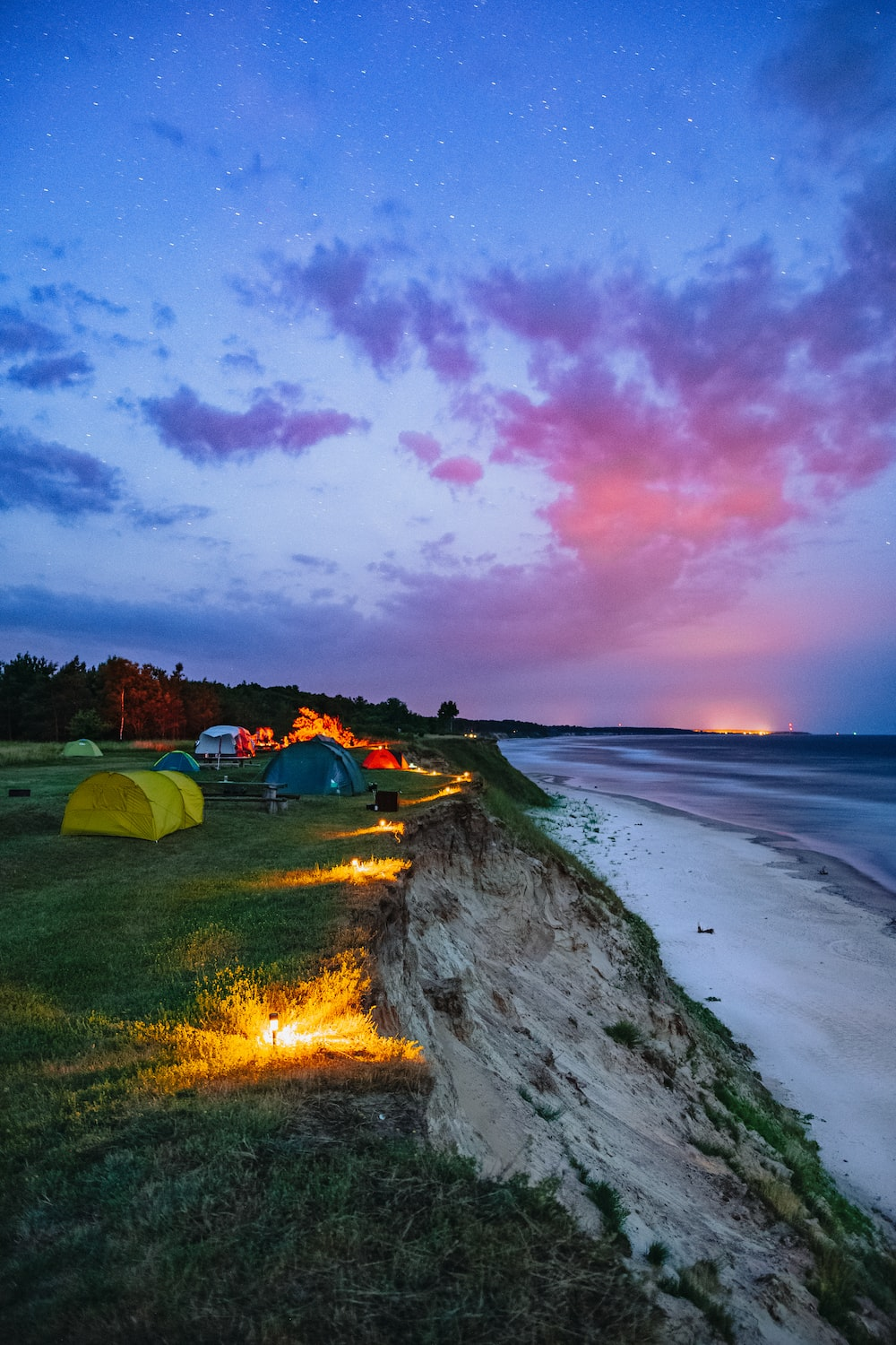 green tent on seashore during sunset