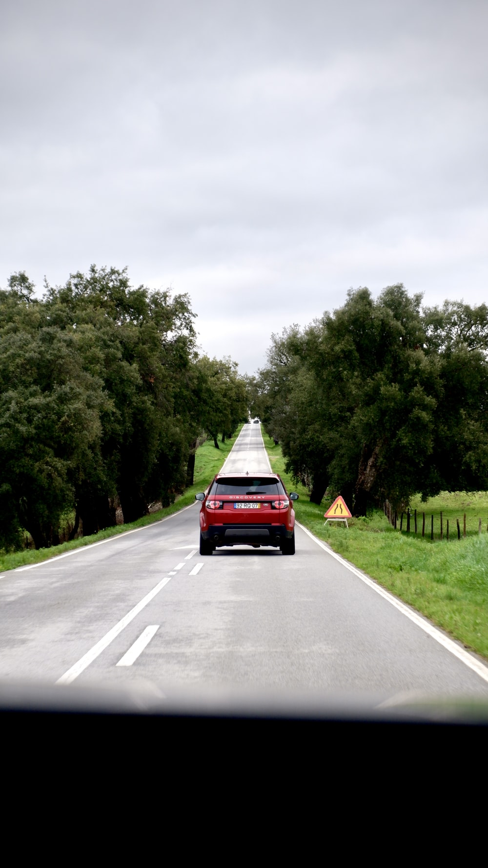 red car on gray asphalt road during daytime