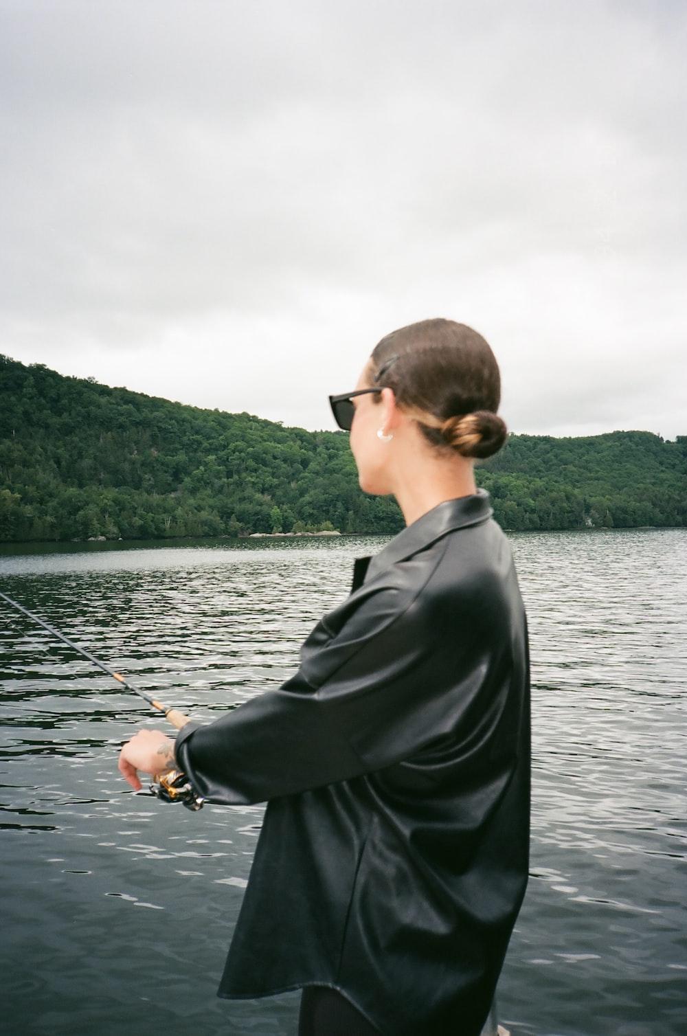 man in black suit jacket holding black fishing rod