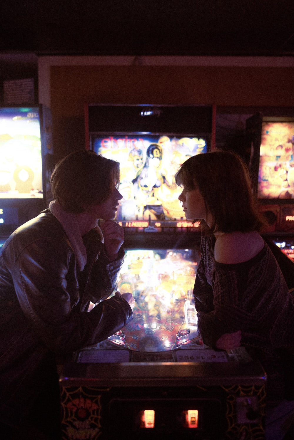 man and woman sitting in front of black flat screen tv