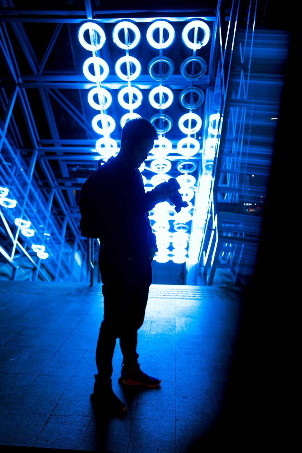 silhouette of man standing in front of lighted wall