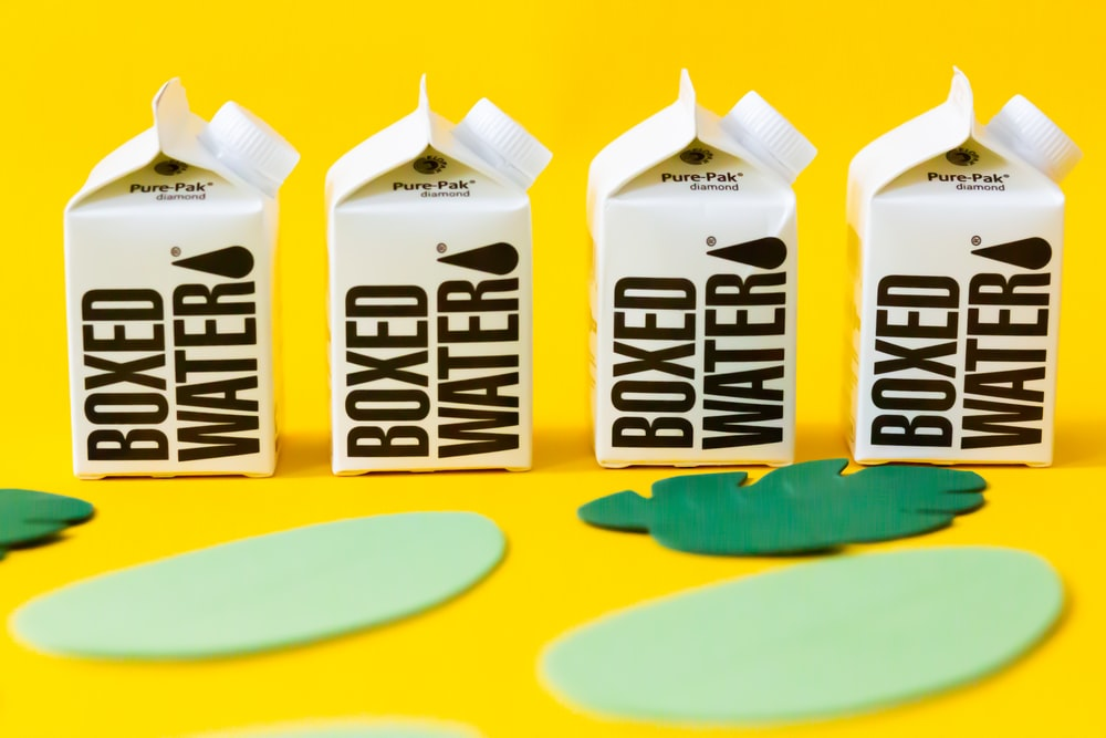 two white and blue milk carton on yellow and blue table