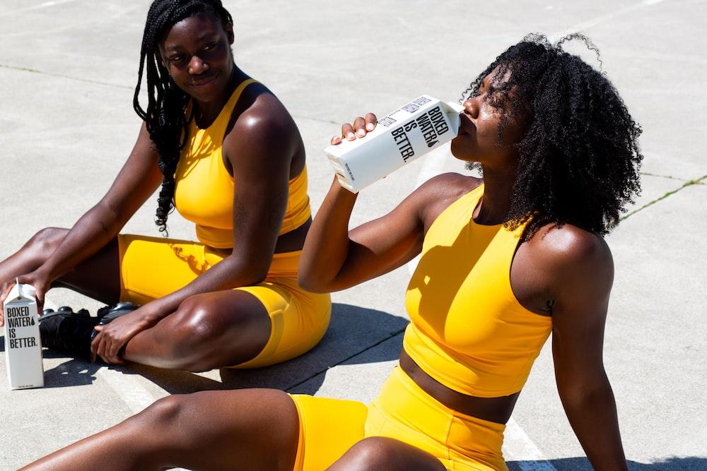 2 women in yellow and black bikini sitting on beach during daytime