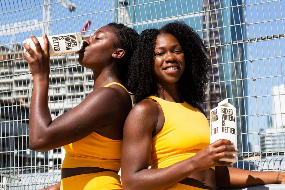 2 women in yellow tank top holding white and yellow labeled box