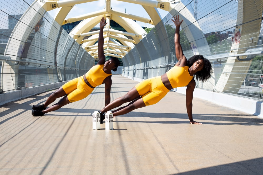 woman in yellow sports bra and yellow shorts jumping on white metal frame