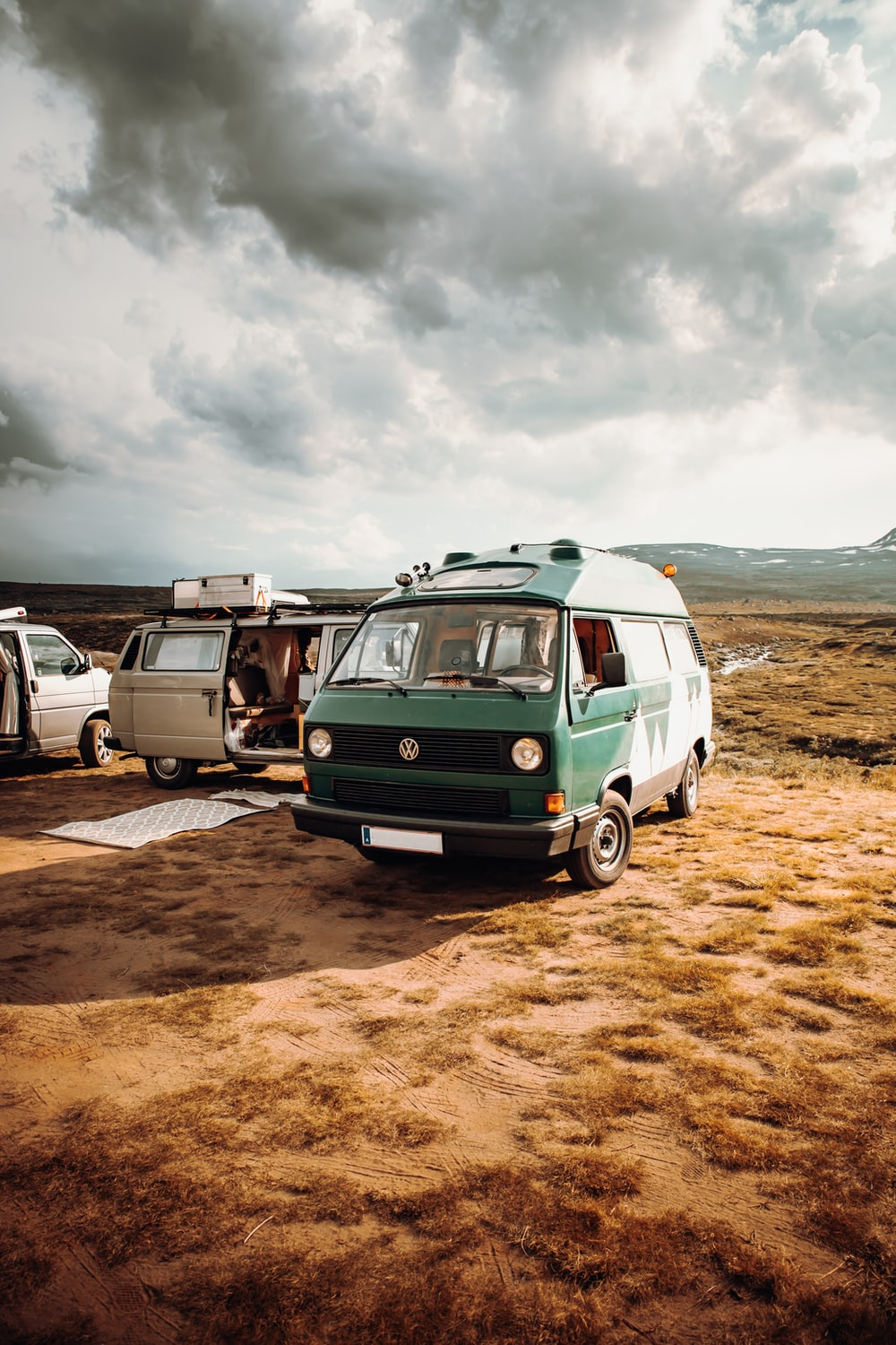 green and white van on brown sand under cloudy sky during daytime