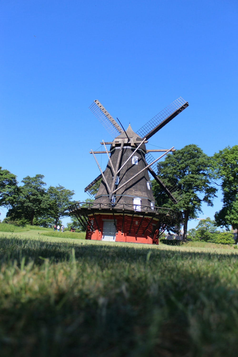 brown and red windmill on green grass field under blue sky during daytime