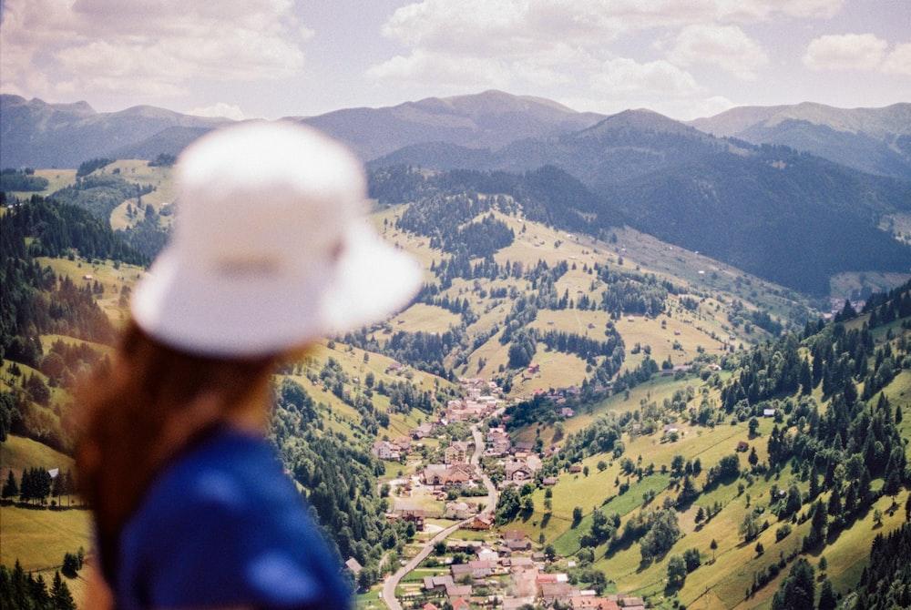 man in blue shirt wearing white cap standing on mountain during daytime