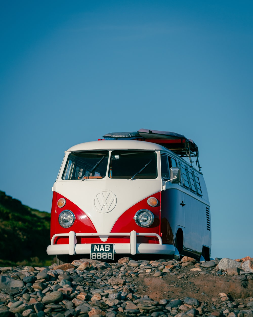 white and red volkswagen t-1 van on gray concrete road during daytime