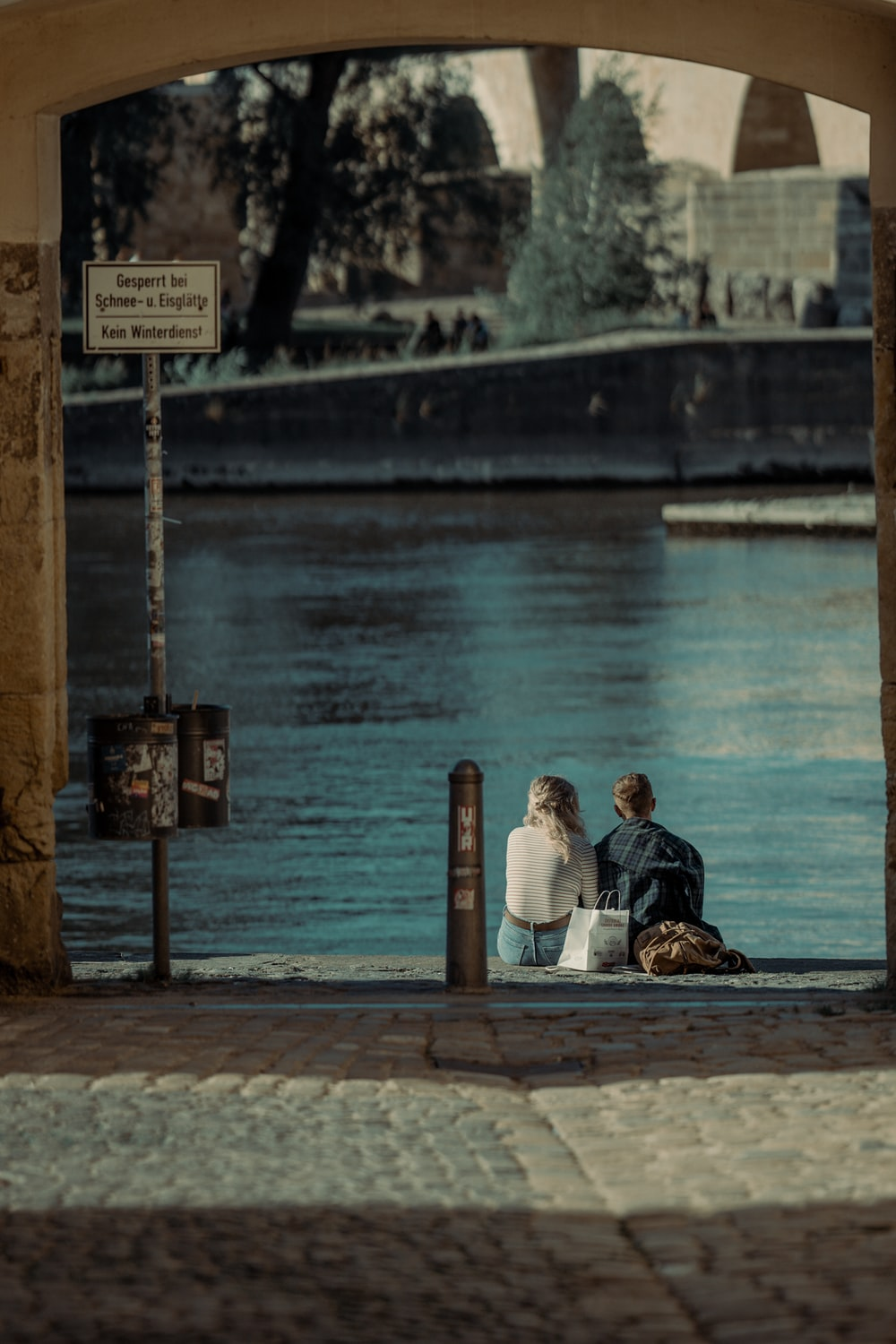 couple sitting on wooden dock during daytime