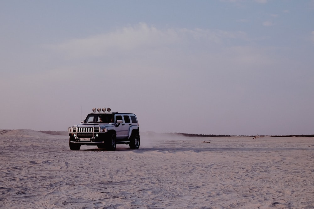 white and black jeep wrangler on brown sand under white sky during daytime