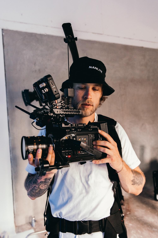 man in white dress shirt holding black video camera