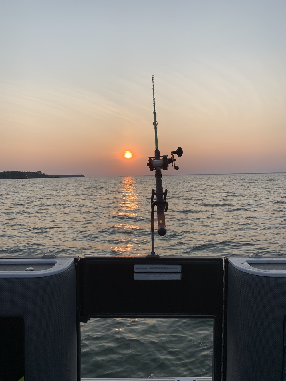 black fishing rod on white boat during sunset