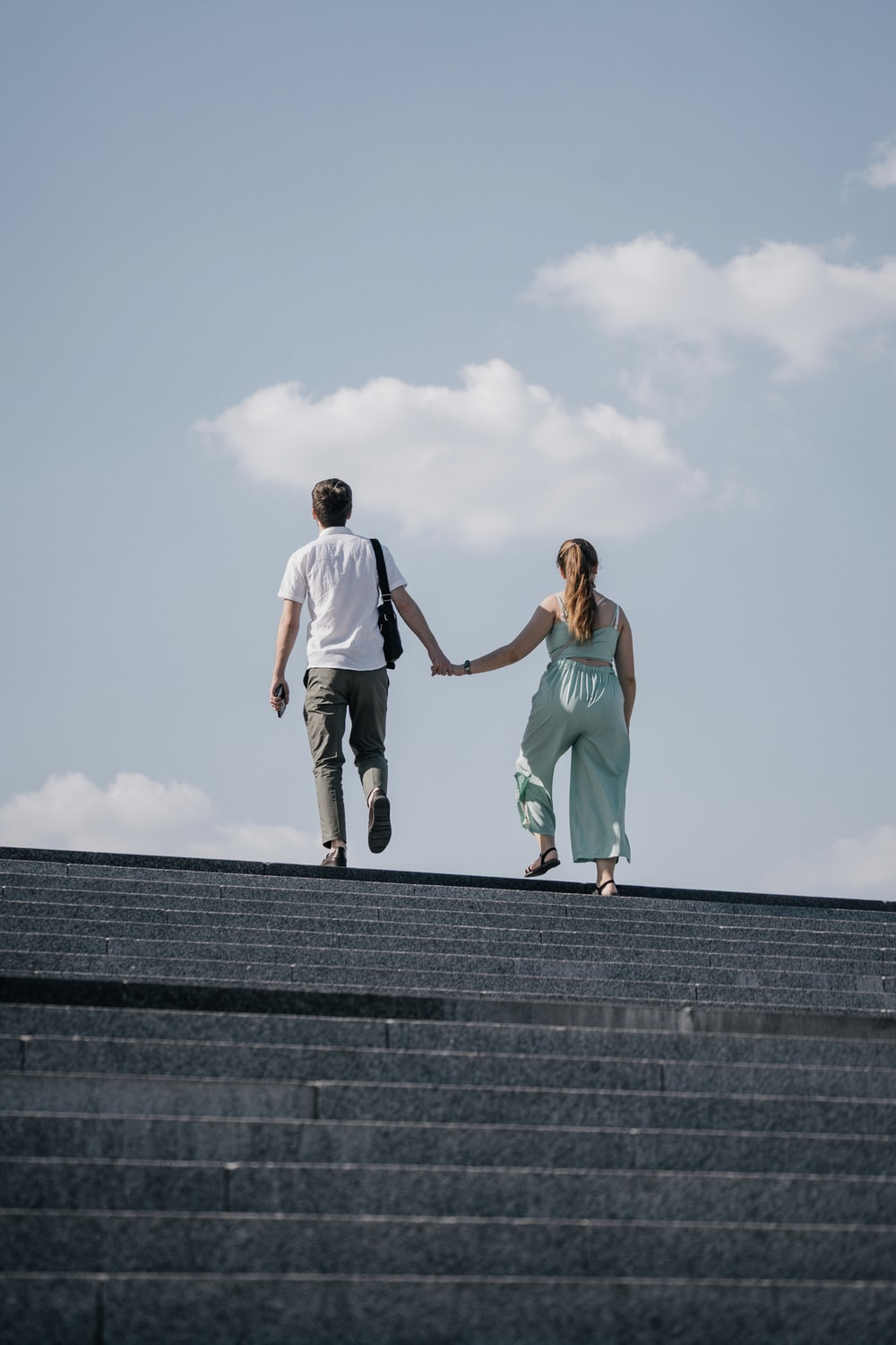 man in white t-shirt and woman in teal tank top on gray concrete stairs during