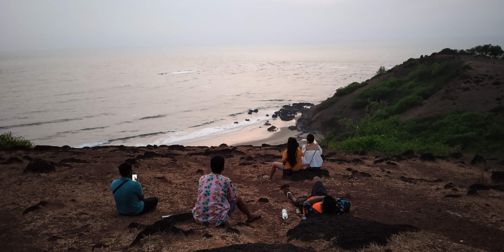 people sitting on brown sand near body of water during daytime