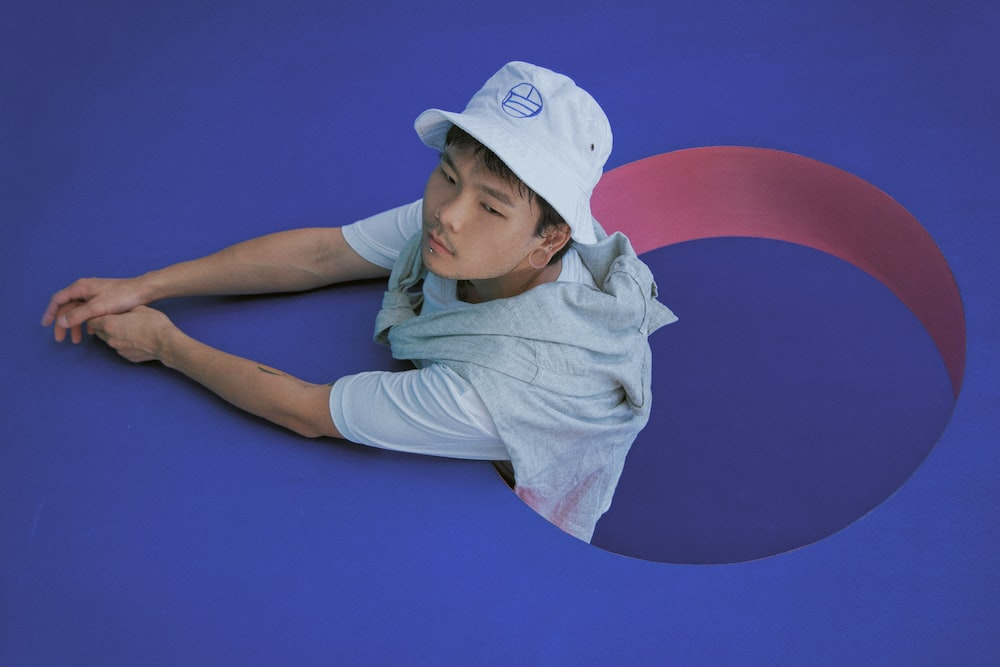 woman in white shirt and white cap lying on blue wall
