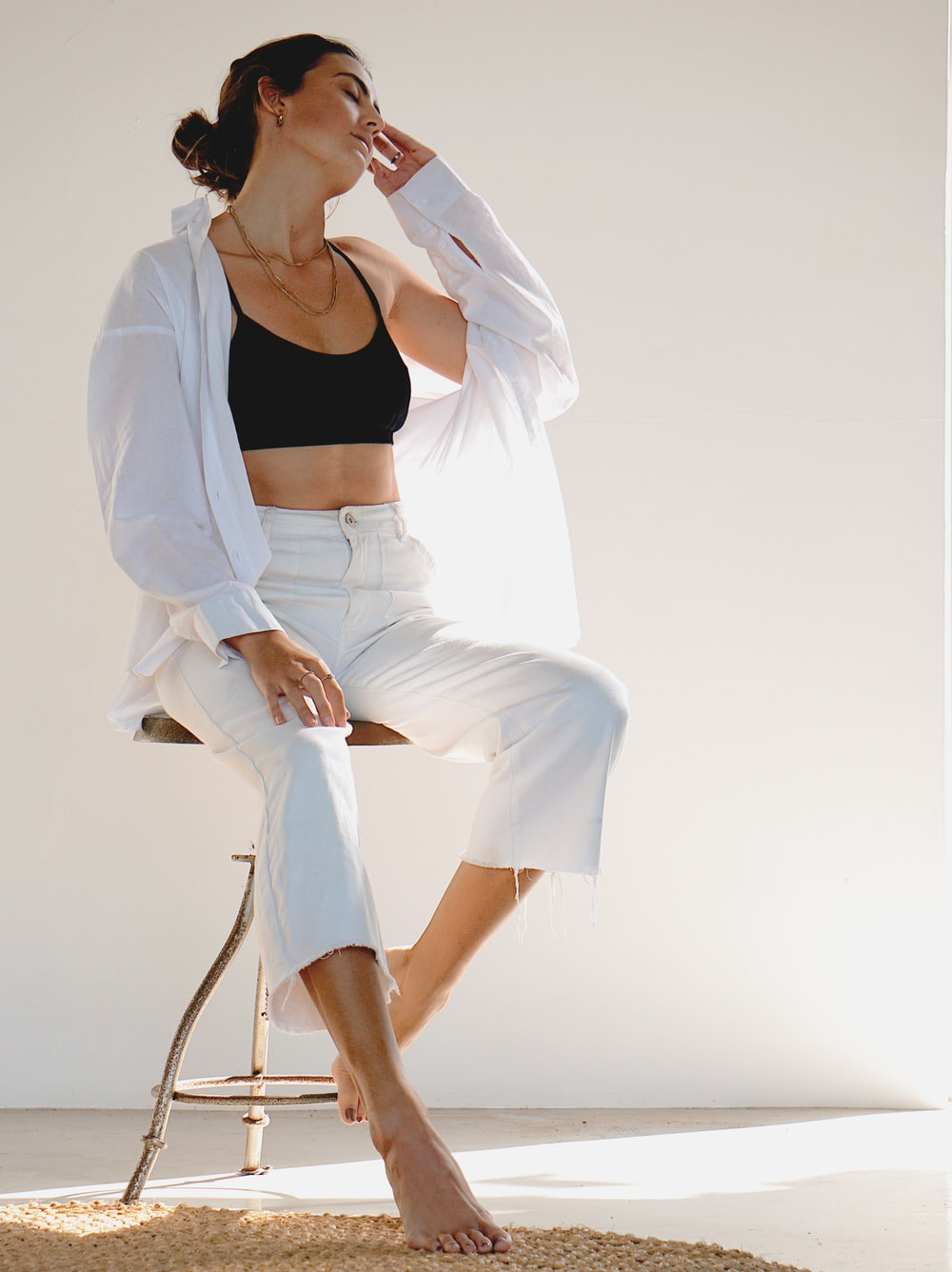 woman in white blazer and white skirt sitting on chair