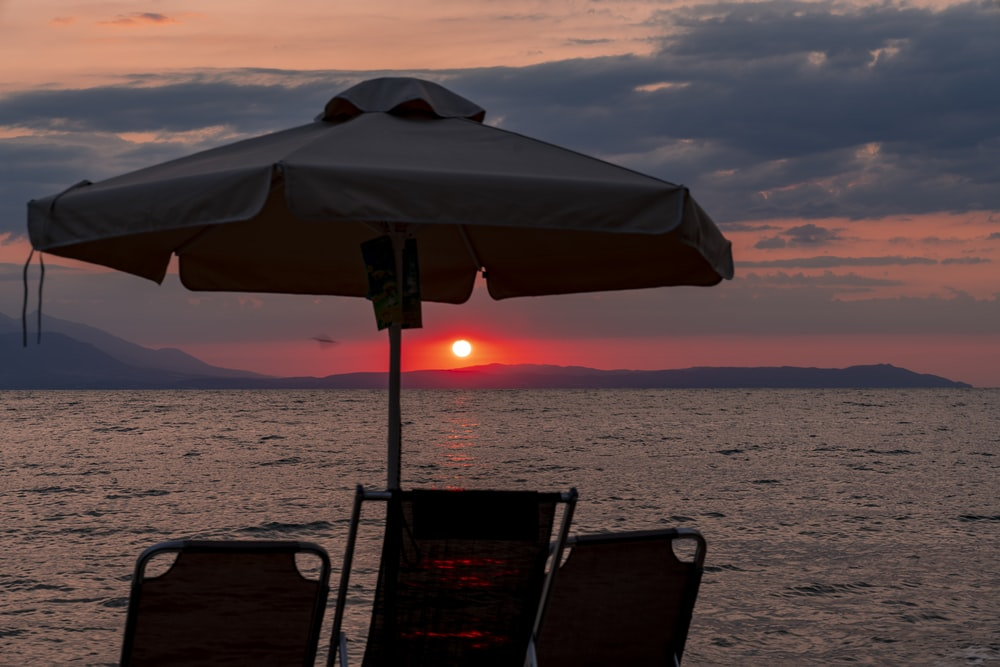 silhouette of two people sitting on chair under blue umbrella during sunset