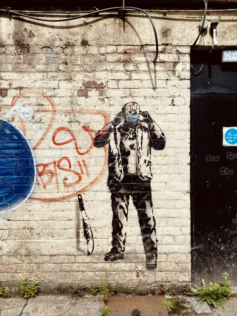 man in black and white camouflage jacket standing beside wall with blue and white graffiti