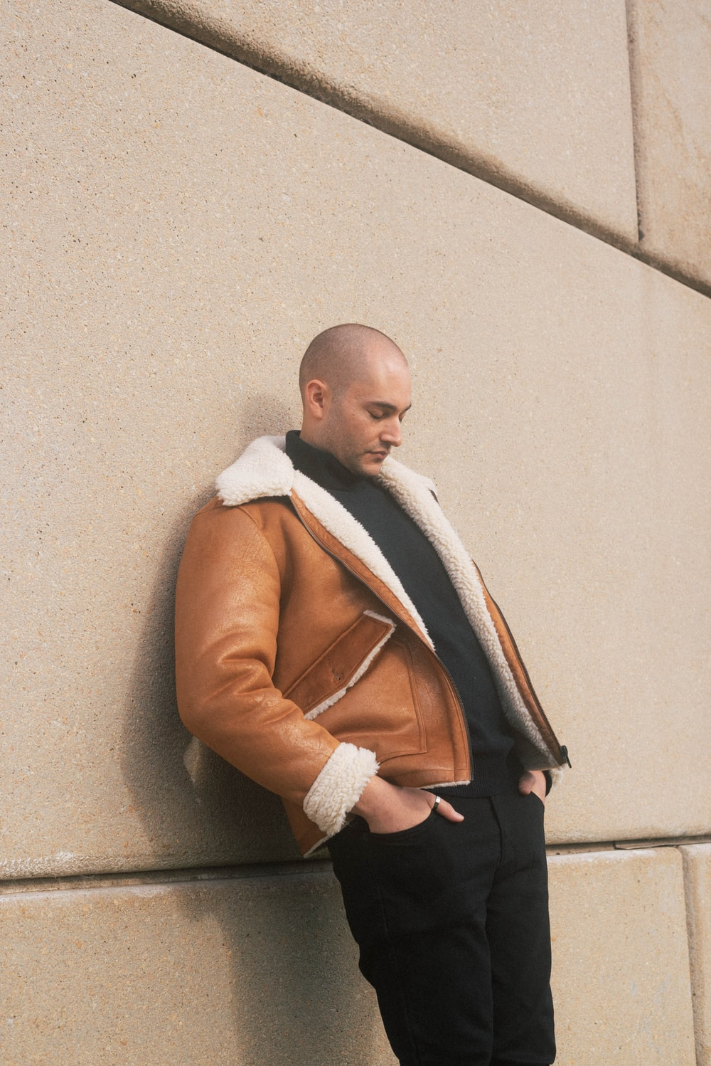 man in brown coat leaning on wall