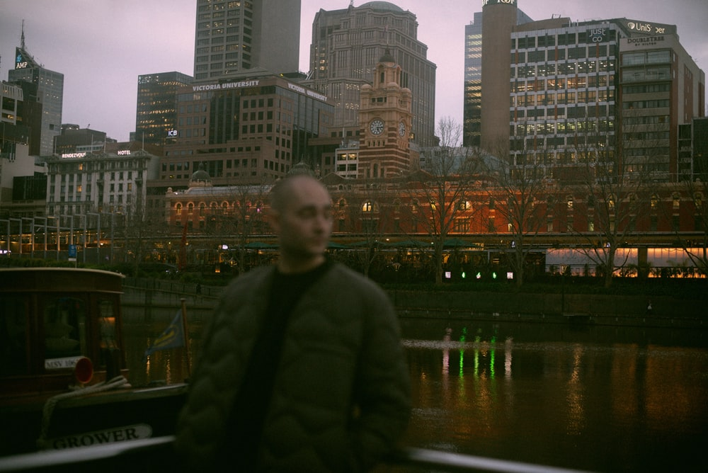 man in green jacket standing near body of water during night time