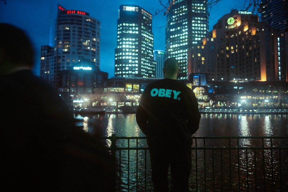 man in black and white hoodie standing in front of city buildings during night time