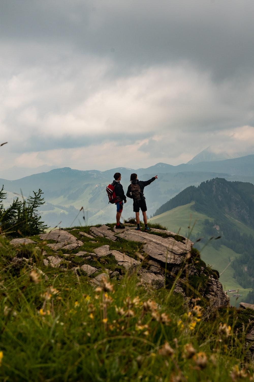 man in black jacket standing on rock mountain during daytime