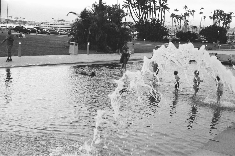 people playing on water fountain in grayscale photography