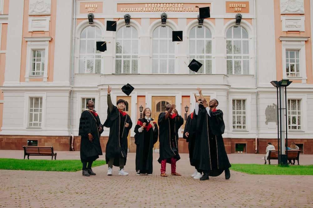 people in black academic dress standing on brown concrete floor during daytime