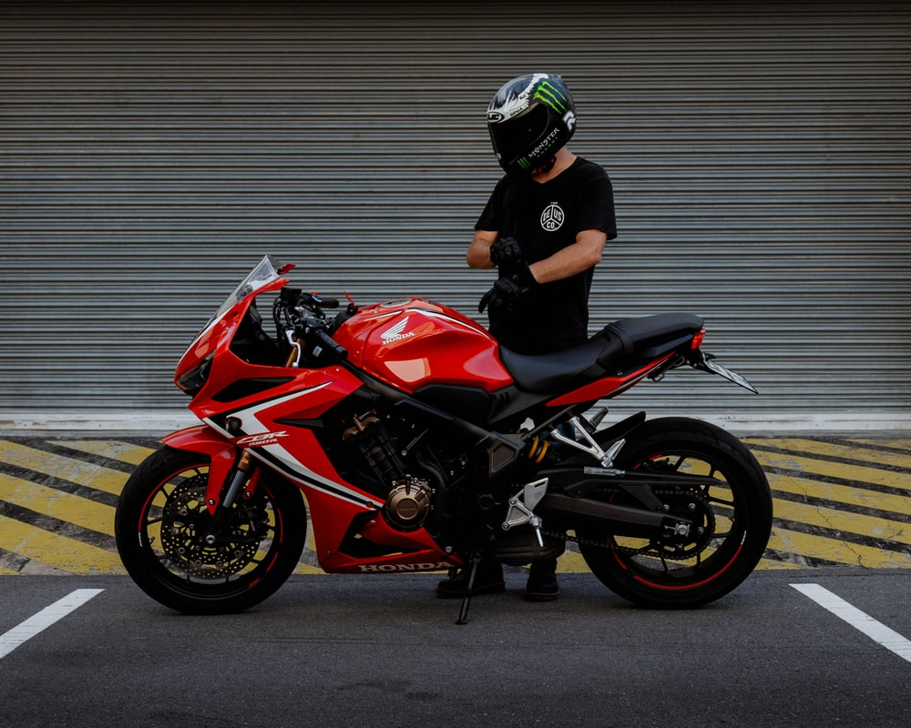 man in black and red motorcycle helmet riding red and black sports bike
