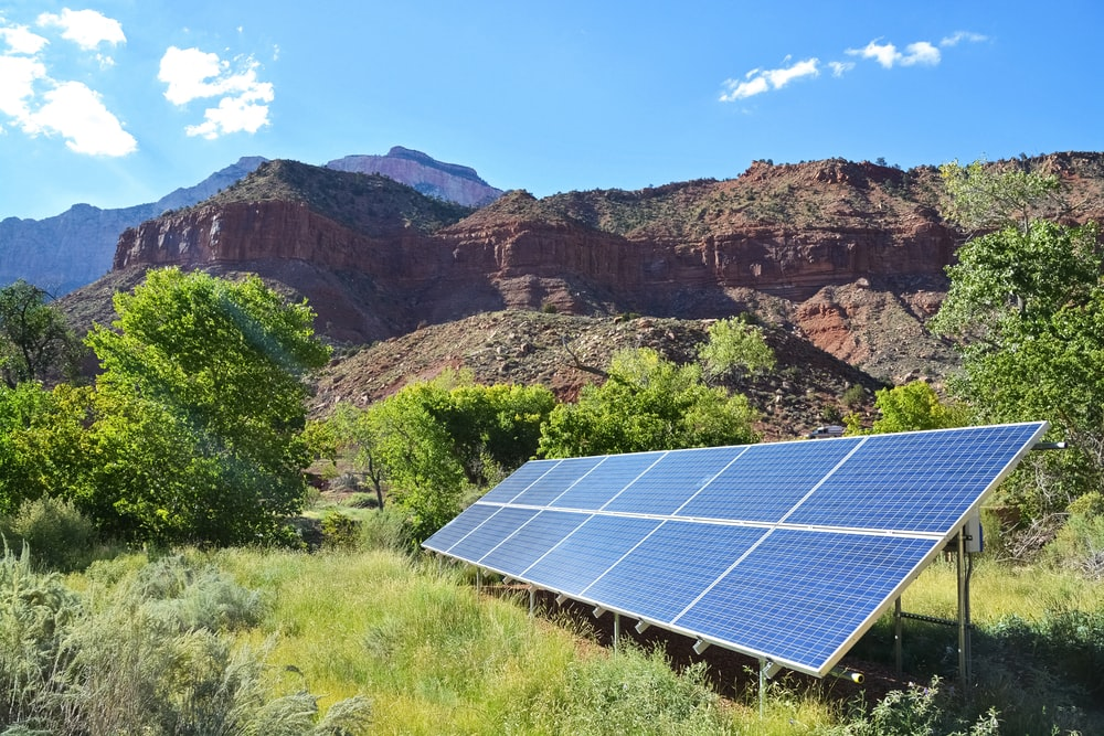 blue solar panel on green grass field near brown rocky mountain during daytime