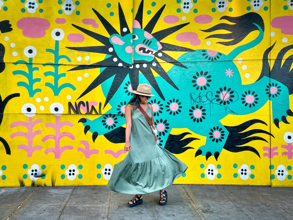 woman in white dress standing near wall with butterfly painting