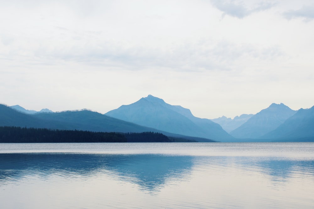 body of water near mountain under white sky during daytime