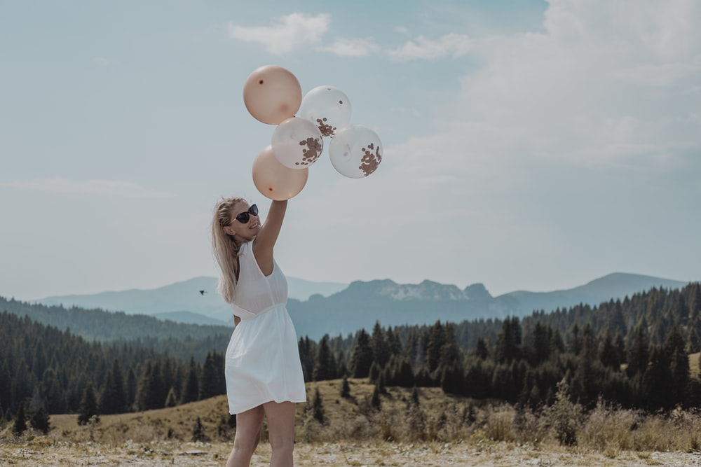 woman in white tank dress holding balloons